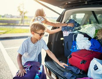 young kid packing car for road trip with luggage in trunk